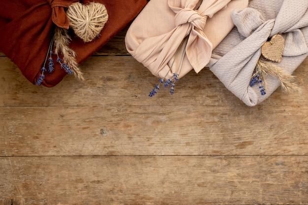 Świąteczne płasko prezentów zapakowanych w stylu furoshiki na drewnianym tle