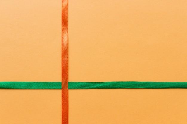 Świąteczne pomarańczowe i zielone wstążki na pomarańczowym tle