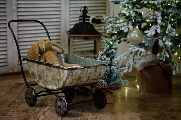 Świąteczne prezenty dla dzieci stoją pod drzewem w sylwestra, pluszowy zając w zabytkowym wózku. idealne tło dla projektu strony, pocztówki lub książki. koncepcja spotkania boże narodzenie i szczęśliwego nowego roku. skopiuj miejsce