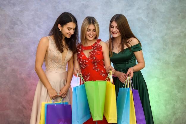 Świąteczne prezenty, trzy młode damy z torebkami pozują w eleganckiej sukience