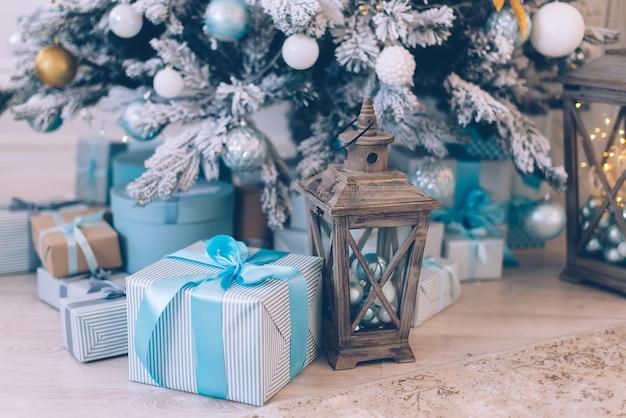 Świąteczne prezenty w pudełkach leżą w pobliżu udekorowanej choinki