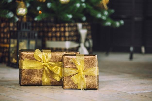 Świąteczne prezenty w złotym papierze do pakowania leżą pod choinką ozdobioną na podłodze