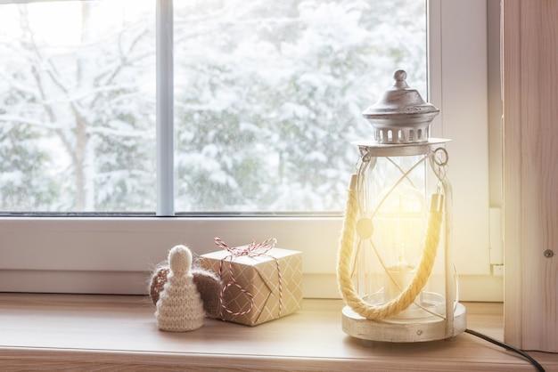 Świąteczne prezenty z latarnią bożonarodzeniową i anioł na drewnianym parapecie zimą w pomieszczeniu