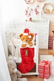Świąteczne przedszkole, pokój zabaw dla dzieci urządzony na nowy rok, biała sypialnia dla dzieci, świąteczne zabawki i prezenty w sypialni dla dzieci, białe łóżko z miękkimi zabawkami