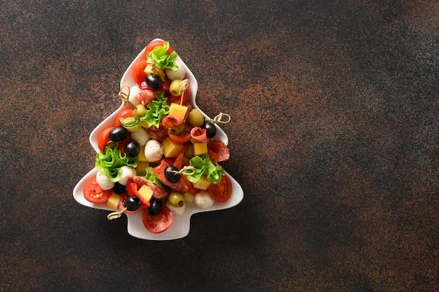 Świąteczne przekąski jako kanapki w kształcie talerza choinki na przyjęcie bożonarodzeniowe na brązowym tle.