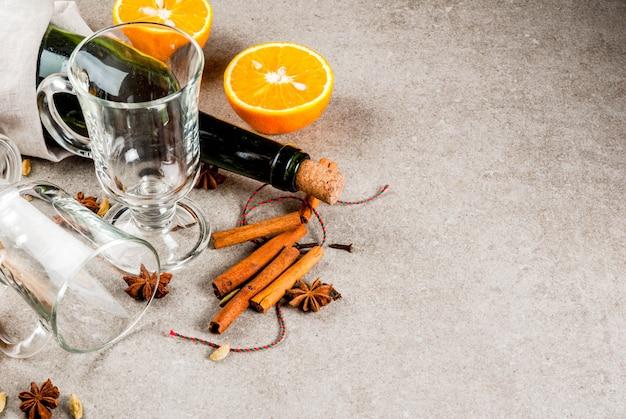 Świąteczne przepisy na gorące napoje, zestaw składników do grzanego wina: butelka wina, szklane kubki, przyprawy, pomarańcza, miejsce