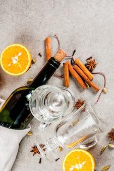 Świąteczne przepisy na gorące napoje, zestaw składników do grzanego wina: butelka wina, szklane kubki, przyprawy, pomarańcza. szarości kamienny tło, copyspace odgórny widok