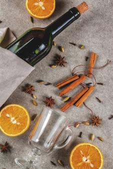 Świąteczne przepisy na gorące napoje, zestaw składników do grzanego wina: butelka wina, szklane kubki, przyprawy, pomarańcza