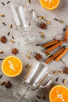 Świąteczne przepisy na gorące napoje zestaw składników do grzanego wina: dwie szklane szklanki przypraw pomarańczowych.
