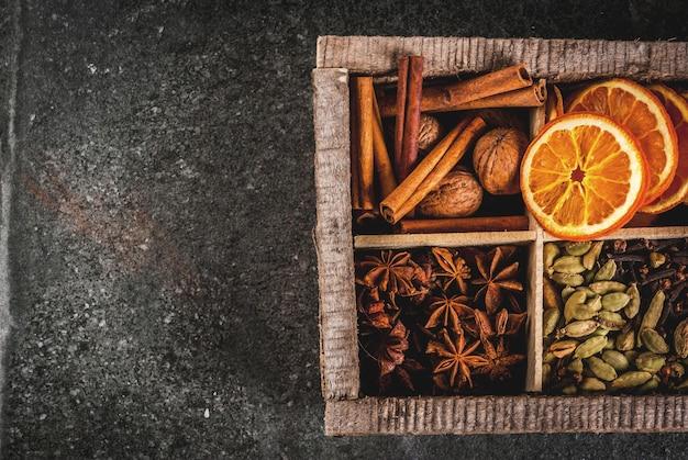 Świąteczne przyprawy do pieczenia, koktajle, grzane wino, pierniki (gwiazdki) - suszone jabłko, pomarańcza, kardamon, goździki, cynamon, anyż. stare drewniane pudełko, czarny kamienny stół. widok z góry miejsca kopiowania