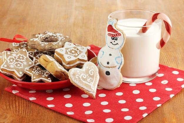 Świąteczne przysmaki na talerzu i szklanka mleka na drewnianym stole z bliska