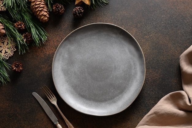 Świąteczne przytulne nakrycie stołu z pustym szarym talerzem na brązowym stole.