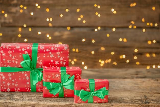 Świąteczne pudełka na prezenty na drewnianym tle z nieostrymi światłami