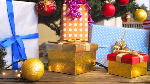Świąteczne pudełka na prezenty w papierowym opakowaniu i kolorowe bombki w salonie