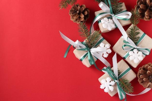 Świąteczne pudełka na prezenty z zielonymi i białymi wstążkami na czerwonej powierzchni