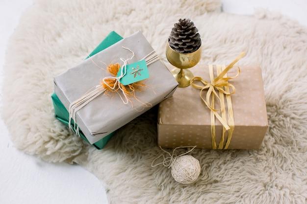 Świąteczne pudełka z prezentami leżącymi na futrzanym dywanie