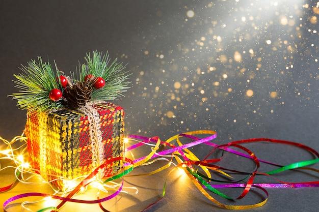 Świąteczne pudełko na czarnym tle z girlandą i serpentynami w brokacie. ozdobiona gałązką jodły z jagodami i szyszkami, owinięta w ciepłą owijkę z dzianiny. nowy rok. skopiuj miejsce