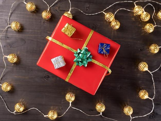 Świąteczne pudełko na drewnianym tle z drobnymi prezentami i lampką bożonarodzeniową. wesołych ferii zimowych.