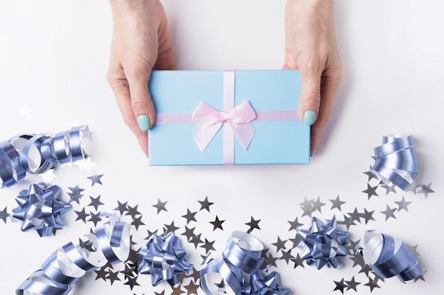 Świąteczne pudełko na prezent w kobiecej dłoni i na granicy gwiazdy srebrna i niebieska gwiazda, blichtr, brokat na białym tle. boże narodzenie. płaski układ. widok z góry z miejsca kopiowania