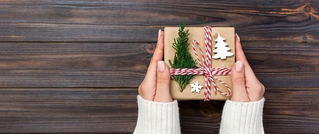 Świąteczne pudełko na prezenty zapakowane w papier z recyklingu, ze wstążką, wstążką na rustykalnym banerze,