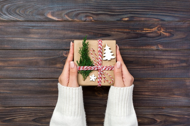 Świąteczne pudełko na prezenty zapakowane w papier z recyklingu, ze wstążką, ze wstążką na rustykalnym drewnie