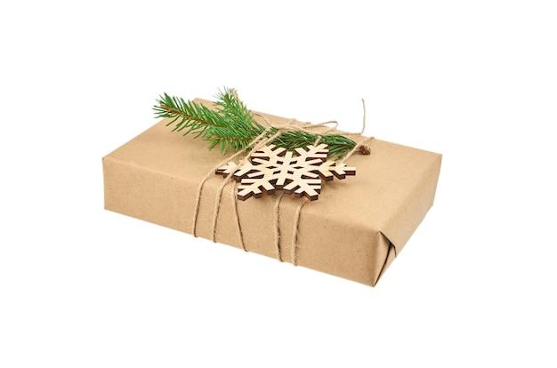 Świąteczne pudełko ozdobione gałązką jodły i drewnianym płatkiem śniegu