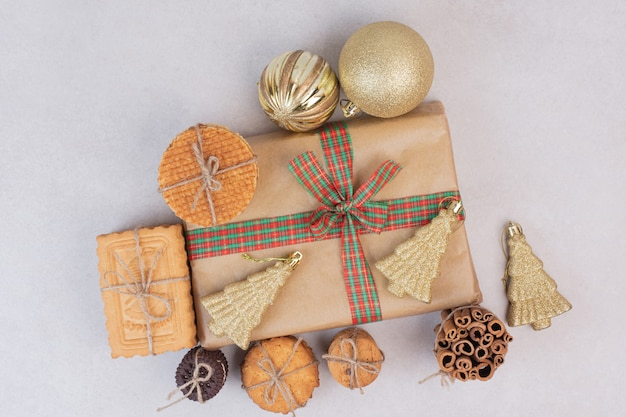 Świąteczne pudełko z ciasteczkami, goframi i laskami cynamonu w sznurku