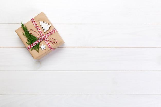 Świąteczne pudełko zapakowane w papier z recyklingu, ze wstążką widok z góry na rustykalny,