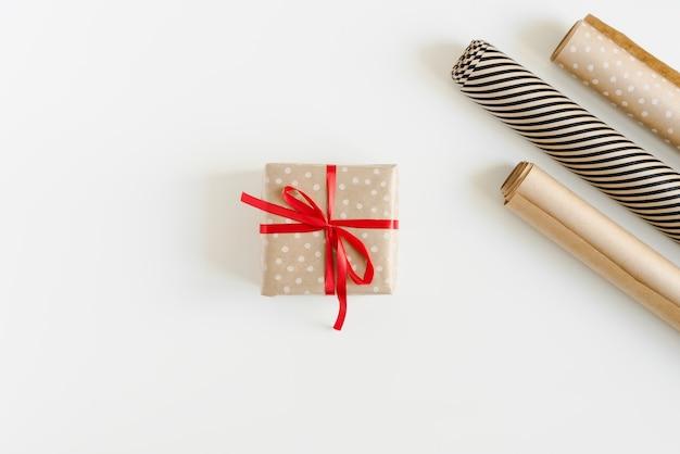 Świąteczne pudełko zawinięte w papier pakowy w kropki z czerwoną wstążką i rolkami papieru na białym stole