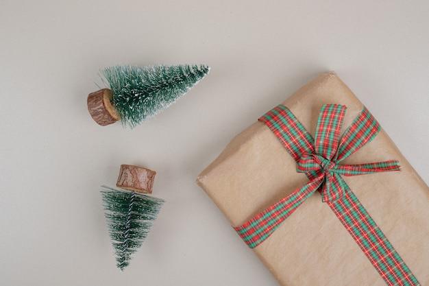 Świąteczne pudełko zawinięte w papier pochodzący z recyklingu z kokardką ze wstążki