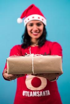 Świąteczne pudełko zawinięte w papier rzemieślniczy na rękach kobiety