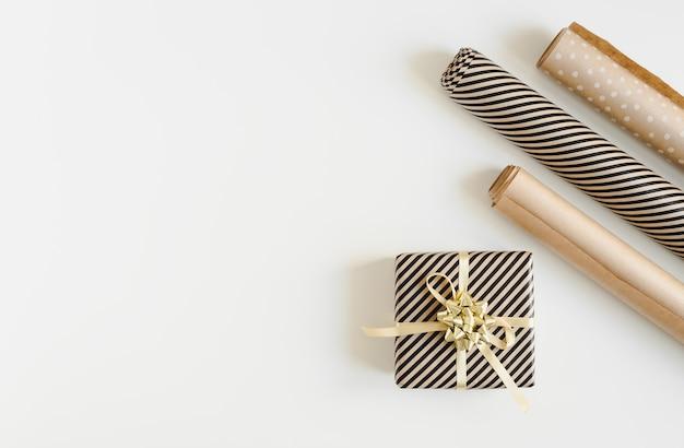 Świąteczne pudełko zawinięte w papier ze złotą wstążką i rolkami papieru kraft.