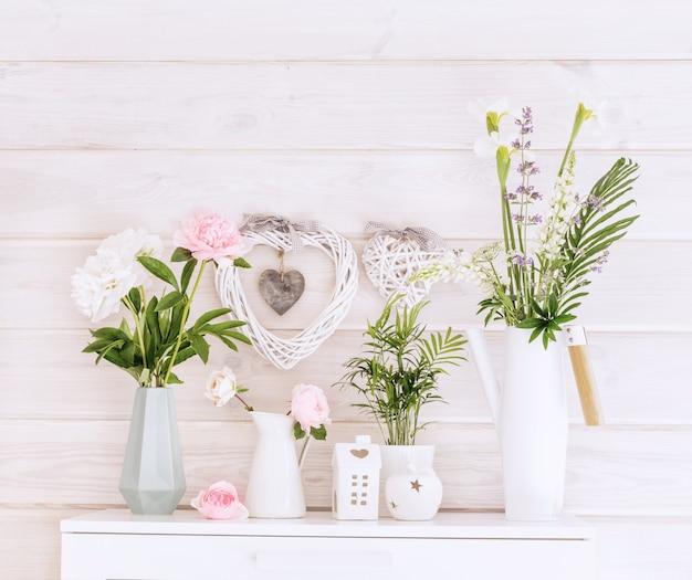 Świąteczne romantyczne bukiety białych i różowych piwonii na białym tle drewnianej ściany, styl skandynawski. ślub, tło walentynki