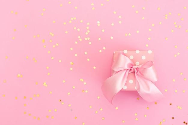 Świąteczne różowe tło. prezent z satynową kokardką i błyszczącymi gwiazdami na jasnoróżowym pastelowym tle.