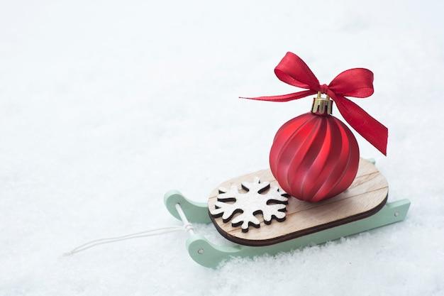 Świąteczne sanie z czerwonym cackiem na śniegu. streszczenie zima kartkę z życzeniami.