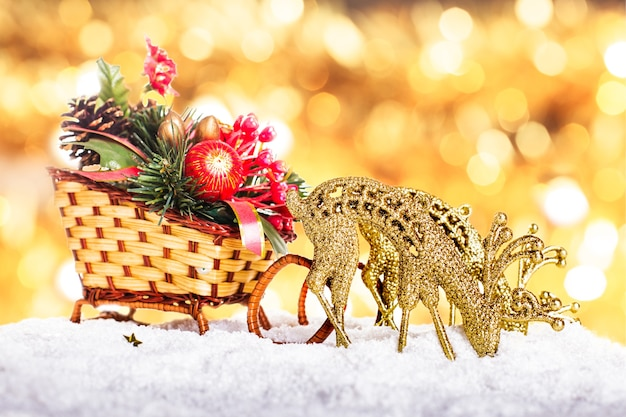 Świąteczne sanie z dekoracją i reniferami na śniegu