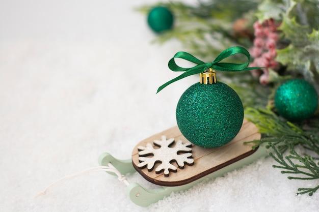 Świąteczne sanie z zieloną bombką na śniegu. streszczenie zima kartkę z życzeniami.