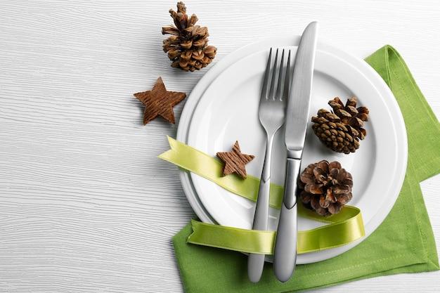 Świąteczne serwowanie sztućców na talerzu i serwetce na jasnym drewnianym stole