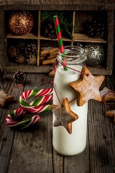 Świąteczne słodycze i smakołyki, butelki z mlekiem dla świętego mikołaja z gwiazdkowymi pierniczkami z dekoracyjną liną i świątecznymi dekoracjami, stara drewniana scena
