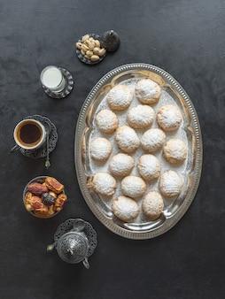 """Świąteczne słodycze ramadan podawane są z herbatą na czarnym stole. egipskie ciasteczka """"kahk el eid"""" - ciasteczka z islamskiej uczty el fitr. widok z góry"""