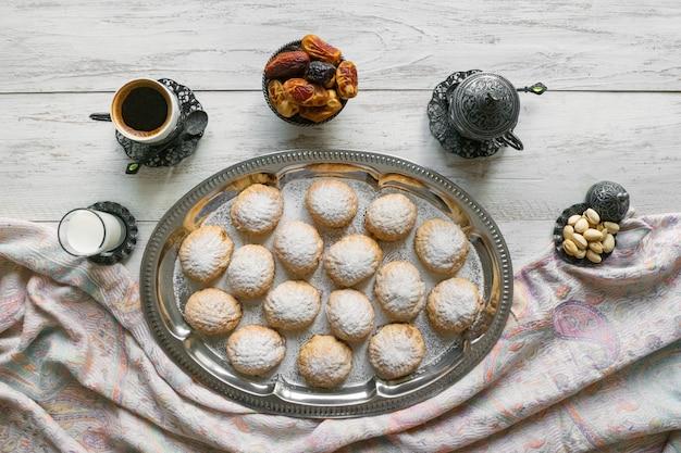 """Świąteczne słodycze ramadan podawane są z herbatą na drewnianym stole. egipskie ciasteczka """"kahk el eid"""" - ciasteczka z islamskiej uczty el fitr. widok z góry"""
