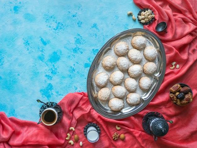 """Świąteczne słodycze ramadan podawane są z herbatą na niebieskim stole. egipskie ciasteczka """"kahk el eid"""" - ciasteczka z islamskiej uczty el fitr. widok z góry"""