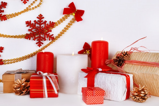 Świąteczne świece na półce na białej ścianie