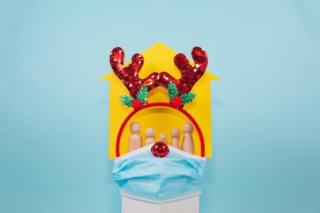 Świąteczne tło boże narodzenie z domem, maską na twarz i rodziną drewna