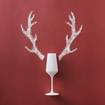 Świąteczne tło boże narodzenie z eleganckim białym szampanem i poroża uformowane z zimowego śniegu na kwadratowym czerwonym tle z copyspace na sezonowe pozdrowienia