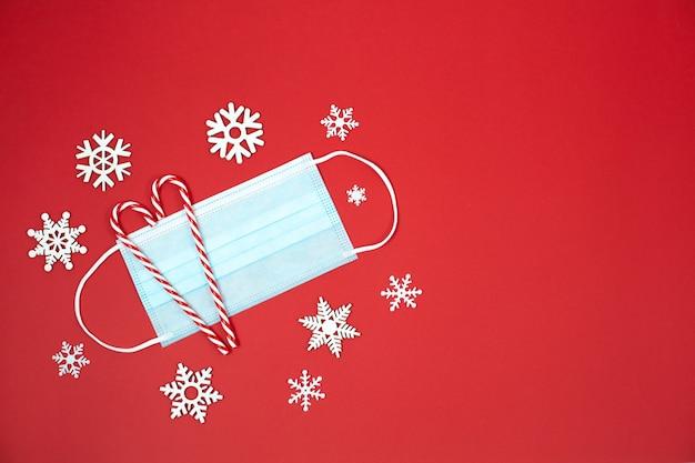 Świąteczne tło boże narodzenie z maską, cukierkiem i płatkami śniegu. nowa normalna koncepcja świąteczna.