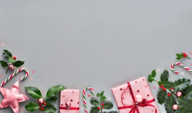 Świąteczne tło boże narodzenie z różowymi pudełkami, paskami cukierków w paski, bibelotami i ozdobnymi gwiazdkami, kreatywny geometryczny układ płaski na szarym papierze z kopią
