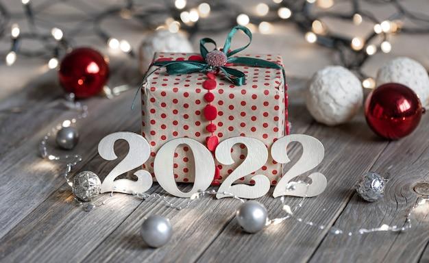 Świąteczne tło bożonarodzeniowe z ozdobnymi numerami i pudełkiem prezentowym