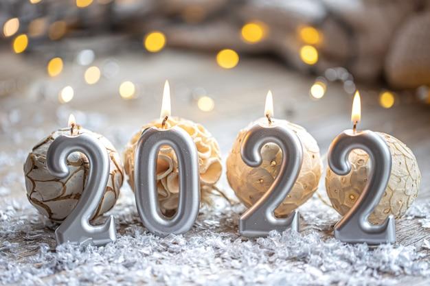 Świąteczne tło bożonarodzeniowe z płonącymi świecami w postaci liczb 2022