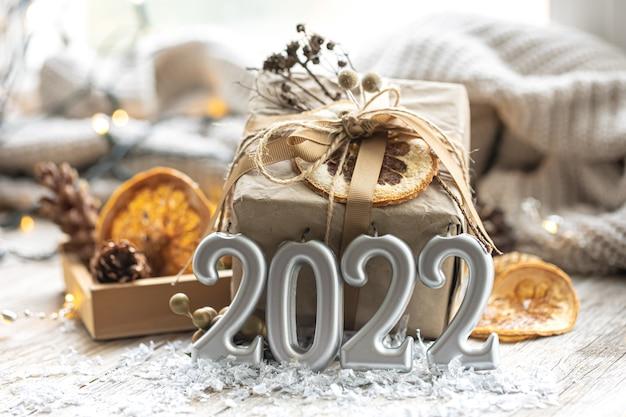 Świąteczne tło bożonarodzeniowe z pudełkiem prezentowym i świecami w postaci cyfr 2022 szczegóły wystroju